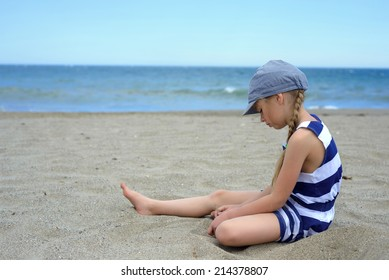 Serious cute little girl sitting on the beach