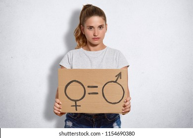 Serious cute young feminist with pony tail, holds plate with sign which demonstrates quality between sexes, dressed in casual t shirt, isolated over white background. Feminism and power concept.