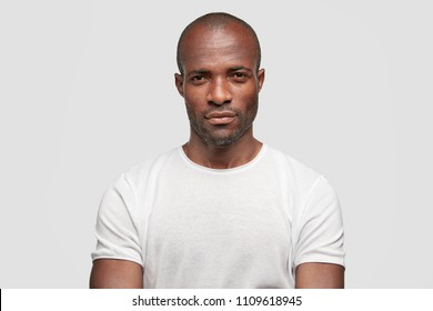 Serious dark skinned businessman has strict look, contemplates about new business project, dressed in casual t shirt, spends free time at office. Studio shot of intelligent male manager indoor
