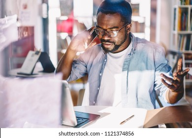 Serious dark skinned male making telephone call to customer support service upset with bad wireless connection in office, angry african american freelancer gesturing during mobile phone conversation