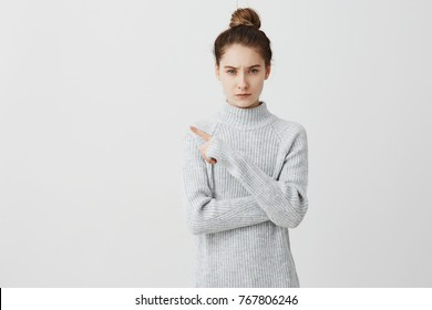 Serious demanding woman pointing index finger to side. Young strict female teacher gesturing frowning paying attention while having class over white background. Human emotions concept