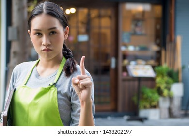 serious and determined woman entrepreneur, small business owner pointing up 1 finger
