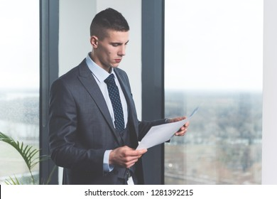 Serious devoted hardworking young bisinessman reading document by the window in his office with the view