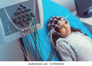Serious diagnostics. Selective focus on an electroencephalography machine with nodes analyzing brain processes of a child lying on an examination couch in the background.