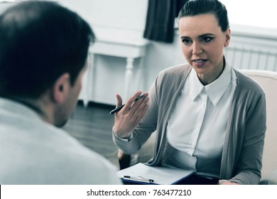 Serious discussion. Professional social worker actively gesticulating while speaking and looking straight into eyes