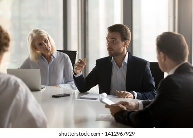 Serious diverse colleagues brainstorm at conference table discuss project at meeting, focused businesspeople talk negotiating in office at briefing, business partners speak considering cooperation