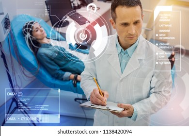 Serious doctor. Attentive qualified doctor making necessary notes while a young woman underdoing electroencephalography behind his back