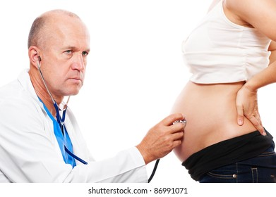 serious doctor attentively listening pregnant woman's belly. isolated on white background