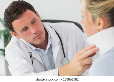 Serious doctor examining neck of a patient in bright office