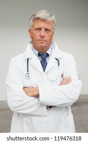 Serious doctor with folded arms in labcoat, Healthcare workers in the Coronavirus Covid19 pandemic