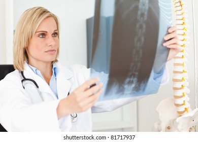 Serious doctor looking at x-ray in her office