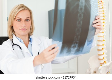 Serious doctor looking at x-ray looks into camera in her office
