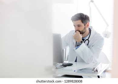 Serious doctor using computer at desk in hospital