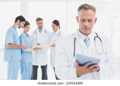 Serious doctor using his tablet with co-workers behind him