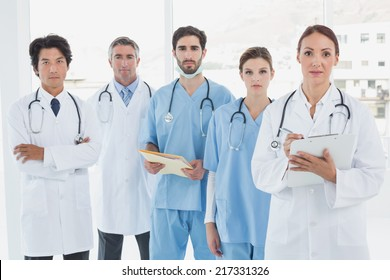 Serious doctors all standing together and looking at the camera