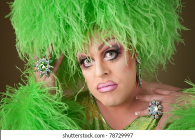 Serious drag queen in green dress with boa wig