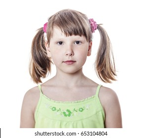 Serious eight year old girl with pigtails, isolated on white