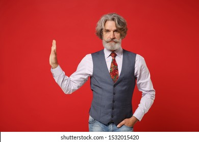 Serious elderly gray-haired mustache bearded man in classic shirt vest colorful tie isolated on red wall background. People lifestyle concept. Mock up copy space. Showing stop gesture aside with palm