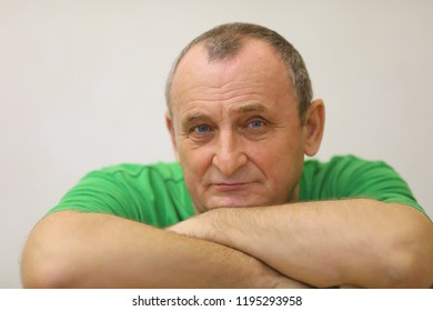 Serious elderly man rests his chin on his arms in green t-shirt in white room, close up portrait