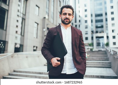 Serious elegant ethnic man in formal suit with paperwork with hand in pocket spending time standing in street looking at camera