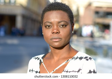 Serious elegant young African woman staring intently at the camera on an urban street in a close up portrait