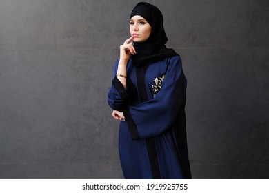 Serious Emirati woman thinking deeply looking far away wearing traditional UAE Abaya and Hijab women's clothing in the Middle East gulf