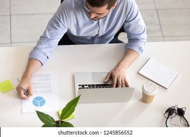 Serious employee using laptop, typing, making notes in report with statistics and analysis at workplace, desk of office worker doing online job, development apps software, focused on project, top view