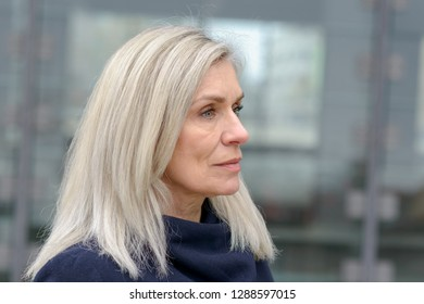 Serious enigmatic middle-aged woman staring thoughtfully off to the right of the frame against a grey urban background