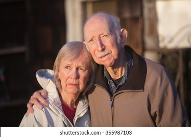 Serious European senior couple standing together outdoors