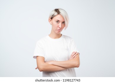 Serious european woman in white t-shirt standing with crossed arms. She listens incredulously to the excuses of her boyfriend.