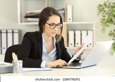 Serious executive entering data in a laptop from a paper document at office
