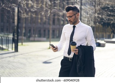 Serious executive manager 40 years old looking news on smartphone holding expensive suit reading email about business using mobile phone with 4G internet near building in new york with tasty drink