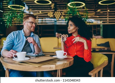 Serious experienced african american director of cafeteria discussing ideas of development business with professional caucasian manager during meeting.Two diverse owners talking about working plan