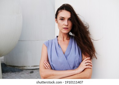 Serious expression of brunette brown hair caucasian European woman, arms crossed while looking at the front camera