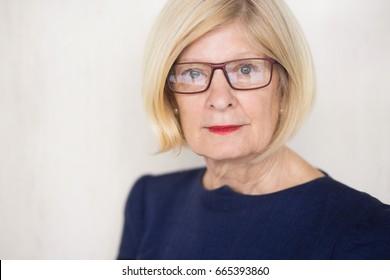 Serious face of senior businesswoman in glasses