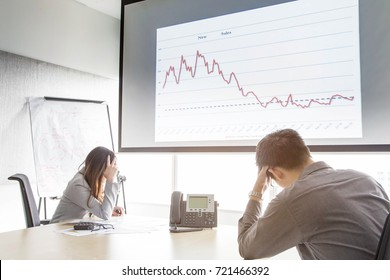 Serious and fail business man and woman in meeting room with  negative graph on screen. They are waiting consultant form conference telephone