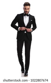 serious fashion model buttoning his tuxedo while walking on white background