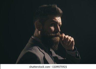 Serious fashionable man with beard&mustache in suit. Handsome stylish bearded man in formal suit. Men's beauty, fashion. Fashion portrait of hipster man. Elegant man with beard touching his mustache.