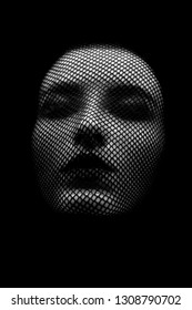 serious female beautiful face with stocking on head, black background, closed eyes, monochrome