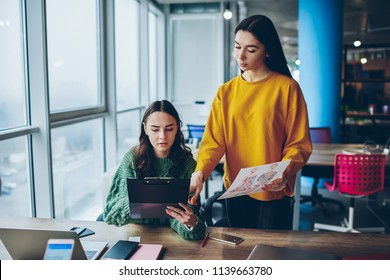 Serious female boss checking work of employee looking at sketches for project, executive manager talking with secretary  about working process planning discussing  information at office together