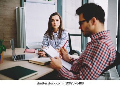 Serious female candidate for occupation looking at male recruiter reading her cv on meeting interview in office, clever woman employee consulting with pensive boss checking report sitting at desktop