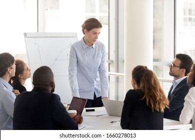 Serious female employee with flip chart at presentation. Woman leader talking with diverse group at meeting room, boss mentor coach holds briefing at negotiation boardroom