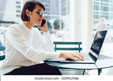 Serious female lawyer in eyeglasses booking tickets during mobile conversation sitting front open laptop with wireless internet connection. Businesswoman talking on cellular while doing remote job