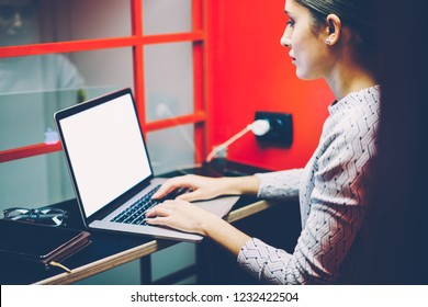Serious female manager typing on laptop computer with mock up screen making preparation for making skype conference in cabin,woman keyboarding on netbook waiting for video call in noise insulance box