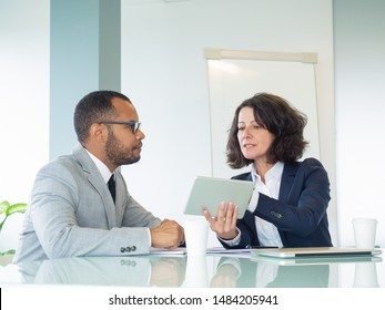 Serious female mentor training male intern. Business woman sitting at meeting table and showing tablet screen to male colleague. Mentorship concept