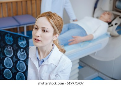 Serious female oncologist examining results of the CT scan