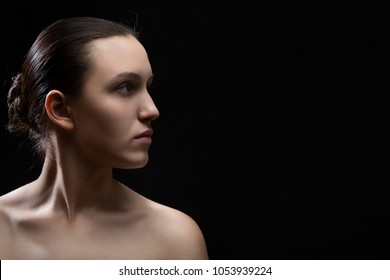 serious female profile on black background with copy space