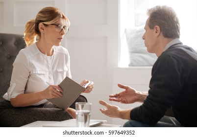 Serious female psychologist listening to her patient