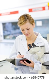 Serious female scientist writing on her clipboard in front of a microscope in her laboratory