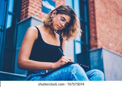 Serious female student in eyeglasses writing creative ideas in notepad sitting outdoors, skilled young hipster girl artist working on sketch during free time drawing in notebook concentrated